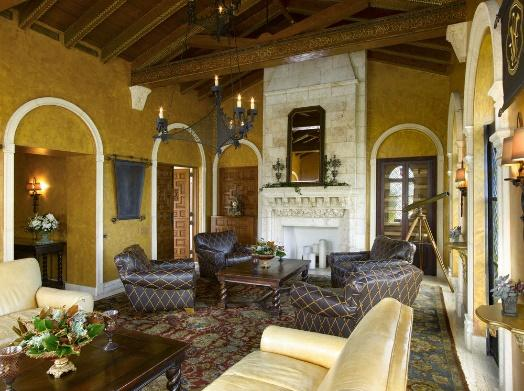 Villas Casa Casuarina luxury sitting room with marble fire place and brown leather chairs