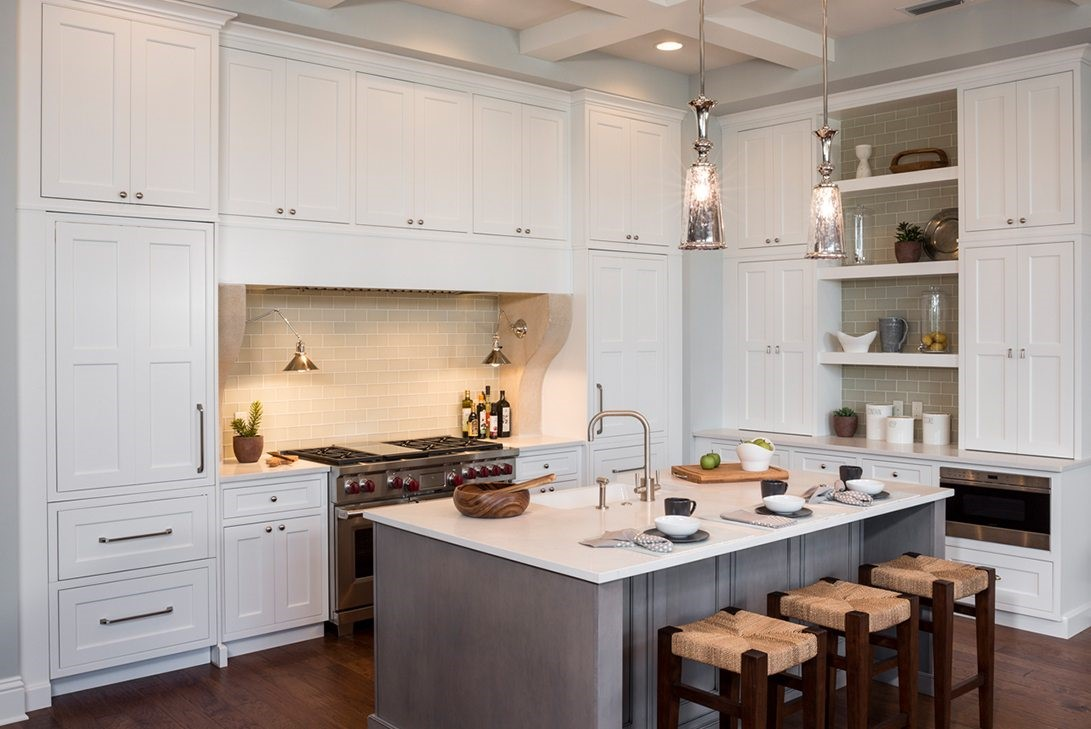 luxury kitchen with white cabinets, a gray island and exotic materials
