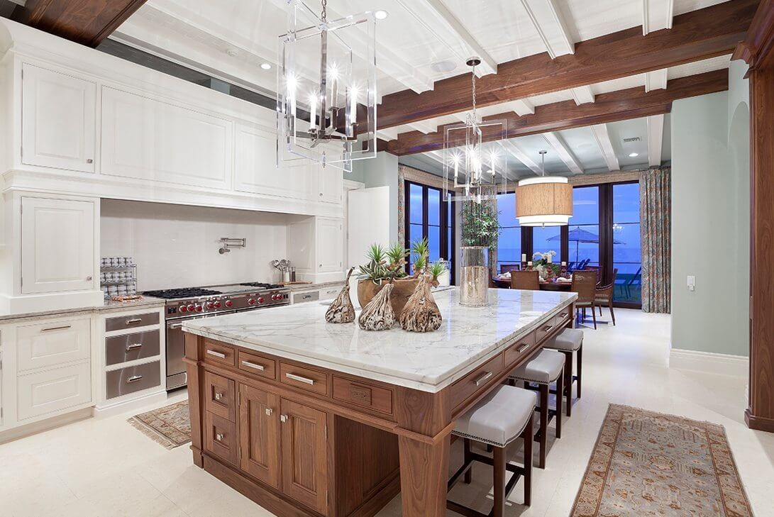 traditional kitchen marble island with wood cabinets and exposed wooden beams