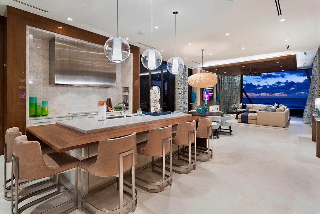 luxury kitchen island with hanging pendant lights and additional seating