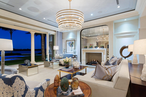 Contemporary designed living room with a large chandelier, a fireplace, and a lakefront view.