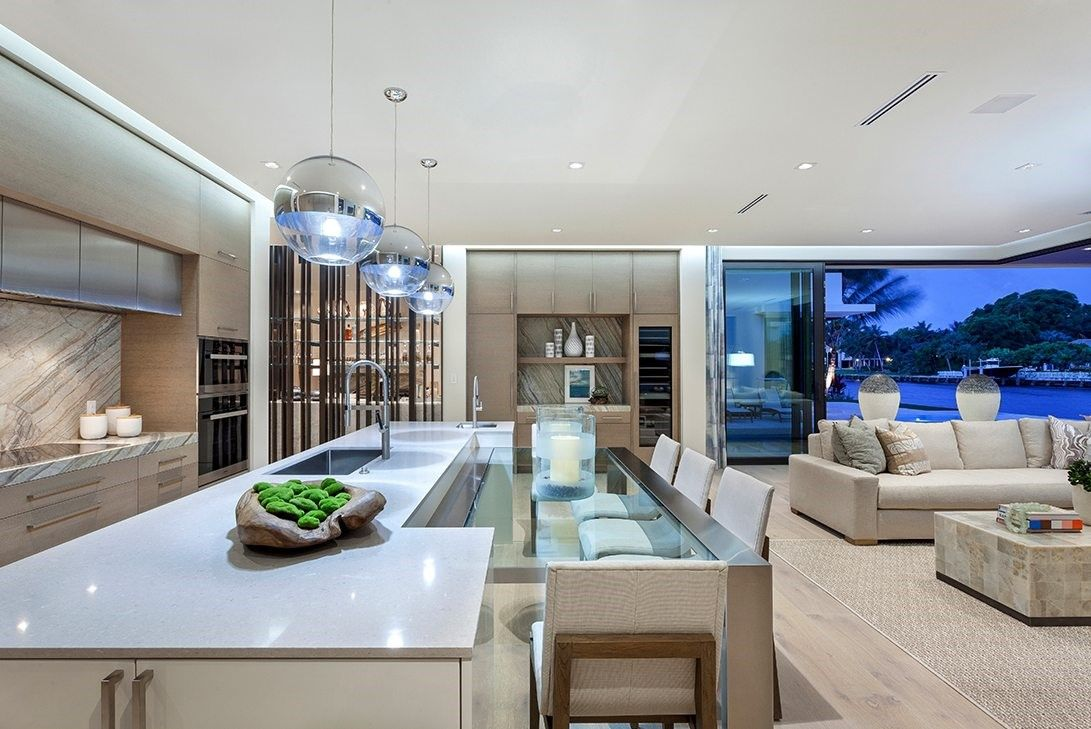 Luxurious kitchen with lighting fixtures above a lengthy island with a dining table extension.