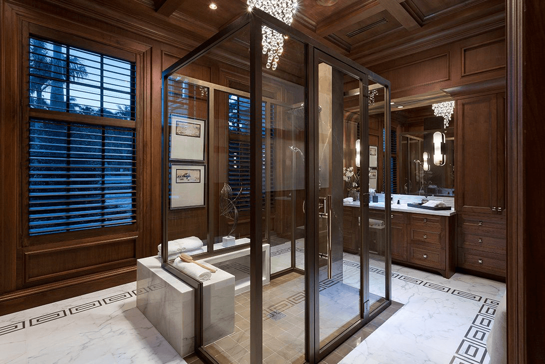 A luxurious bathroom in Palm Beach with a chandelier, mirror sconces, and beautiful lighting acting as accessories.