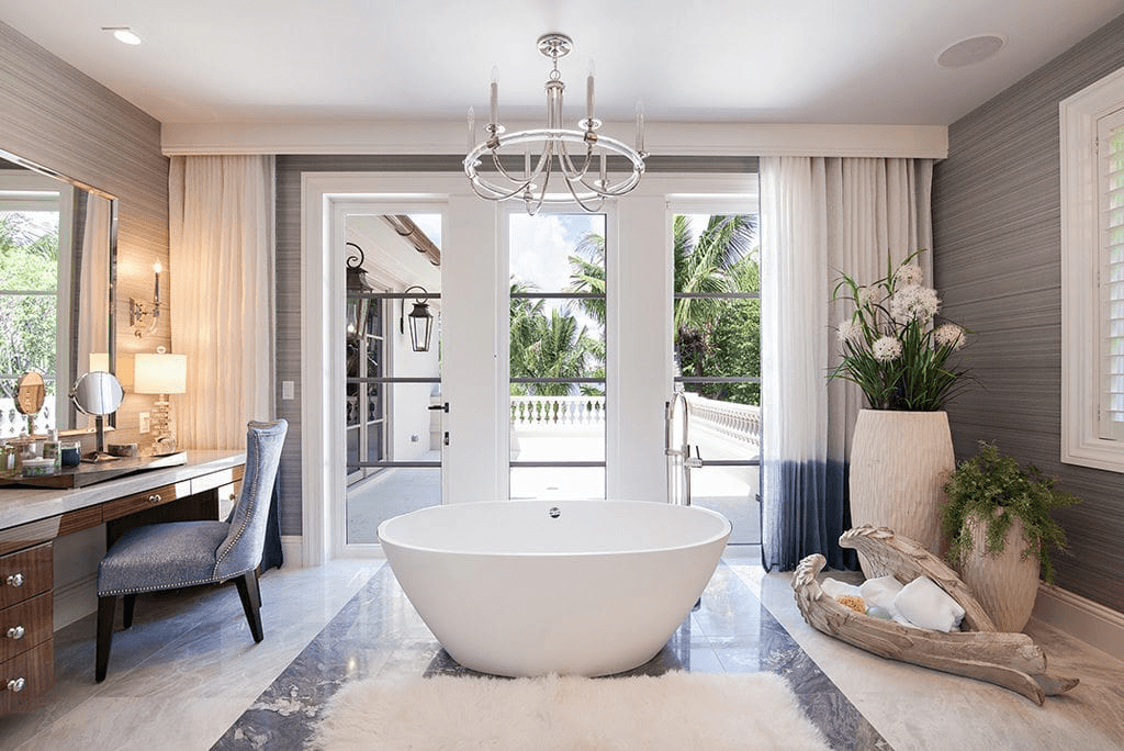 Our Modified Georgian Style design project luxury bathroom with a unique crystal-like chandelier and an oversized soaking tub at its center.