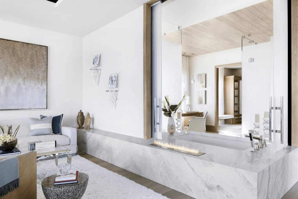 Ocean Ridge contemporary luxury bathroom with a tub surrounded by marble, and a simple fire feature.